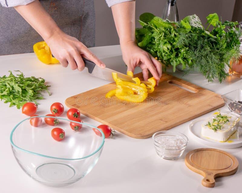 Uma mão do ` s da mulher corta uma pimenta amarela em uma placa de madeira em uma mesa de cozinha branca Preparação da salada fotografia de stock royalty free