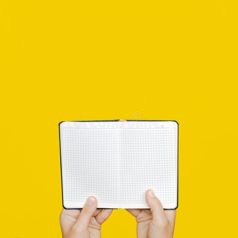 Uma mão do ` s da mulher guarda um caderno fechado azul no fundo amarelo fotografia de stock royalty free
