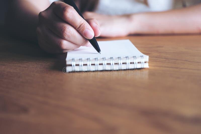 Uma mão do ` s da mulher que escreve para baixo em um caderno vazio branco na tabela de madeira imagens de stock royalty free