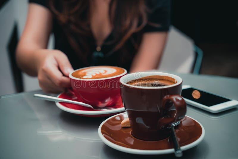 Uma mão do ` s da mulher que guarda o copo de café do latte com o copo de café de Americano e o smartphone na tabela de vidro no  foto de stock royalty free