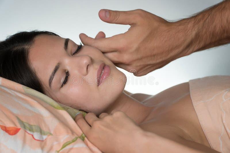 Uma mão do ` s do homem acaricia a cara do ` s da menina na manhã Manhã que desperta Para trás de um fundo branco borrado foto de stock royalty free