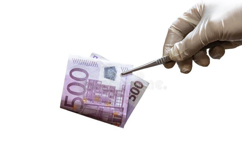 Uma mão em uma luva guarda a pinça com uma conta de cinco cem euro O conceito da corrupção na medicina ou o salário da foto de stock