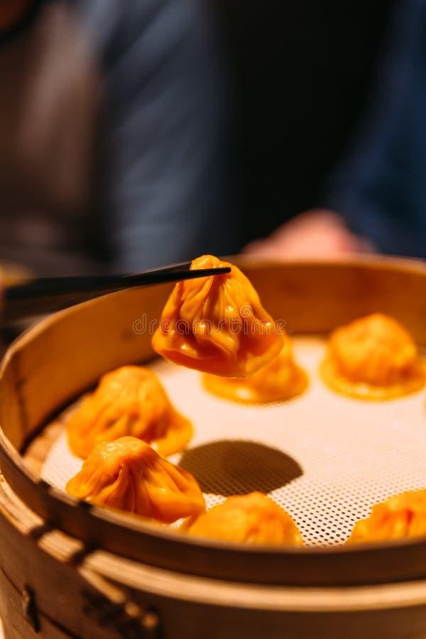 Uma mão está comprimindo a bolinha de massa alaranjada de Foie Gras Xiao Long Bao Chinese Soup da cor com os hashis da flâmula de imagens de stock royalty free