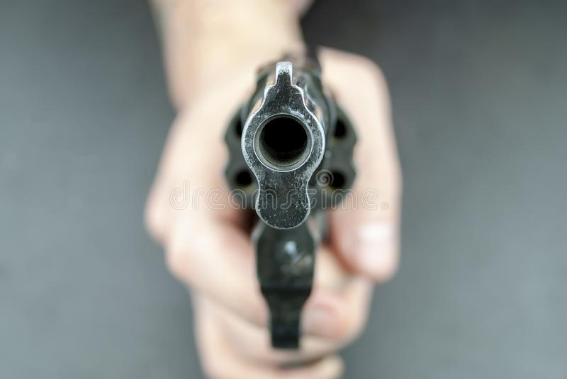Uma mão está guardando um revólver, com o tambor que enfrenta a câmera foto de stock