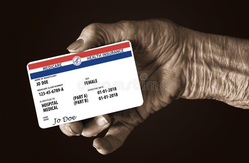 Uma mão fêmea idosa guarda um cartão unido zombaria do seguro de saúde de Medicare do governo estadual É um cartão genérico fotos de stock royalty free