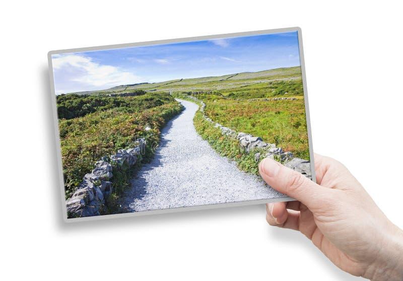 Uma mão fêmea que guarda um cartão sobre um lan liso irlandês típico foto de stock