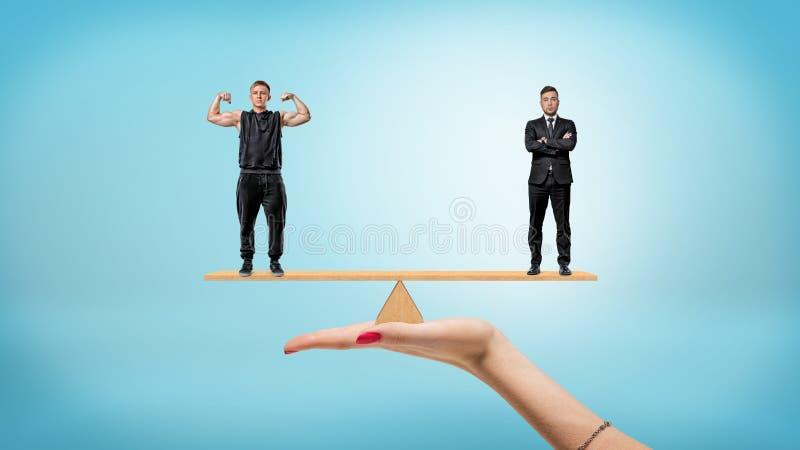 Uma mão fêmea que guarda uma balancê pequena com um homem de negócios um atleta no cada lados fotografia de stock royalty free