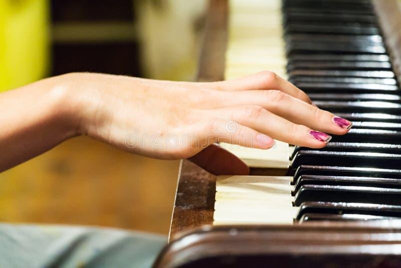 Uma mão fêmea que joga um piano velho do vintage foto de stock royalty free
