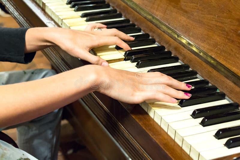 Uma mão fêmea que joga um piano velho do vintage imagens de stock royalty free