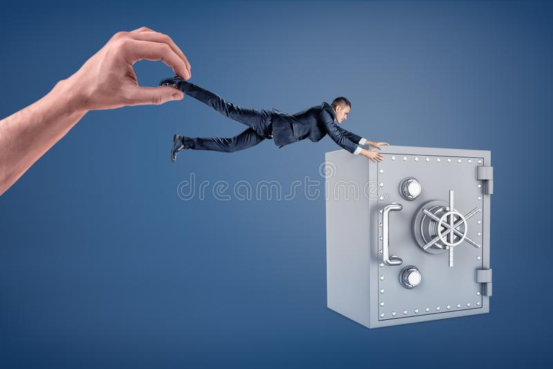 Uma mão gigante guarda um homem de negócios pequeno que não alcance uma grande caixa segura imagem de stock