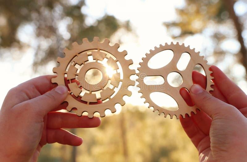 Uma mão guarda as engrenagens na frente de um sol de ajuste Conceito de uma ideia nova, aprendendo e criativo embora fotos de stock