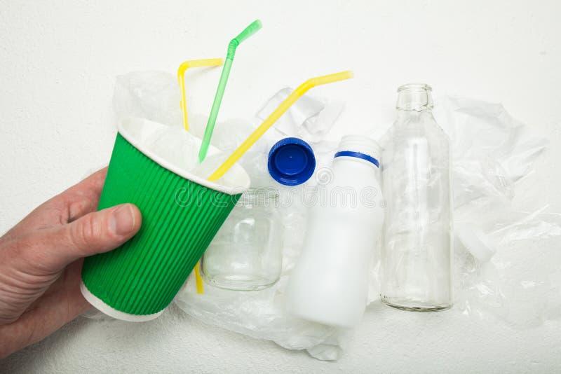 Uma mão guarda um copo de papel usado em um fundo do lixo recycling imagens de stock royalty free