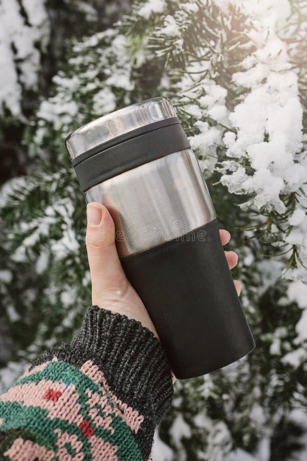 Uma mão i que guarda uma caneca Thermo reusável, garrafa térmica, caneca do curso no fundo de uma árvore conífera coberto de neve fotos de stock royalty free