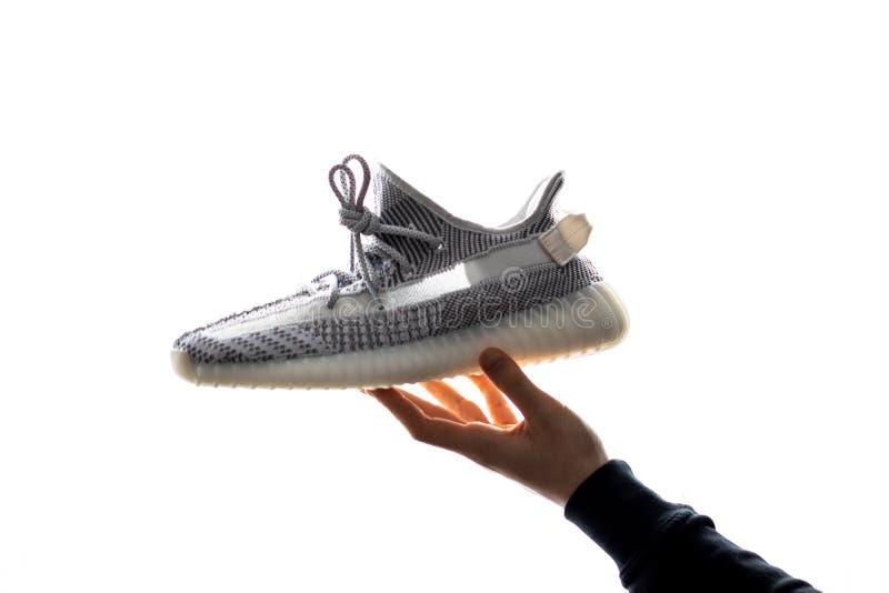 Uma mão mantém Adidas Yeezy 350 V2 estático em sua mão Liberado o 26 de dezembro de 2018 imagens de stock royalty free