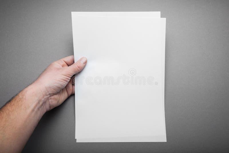 Uma mão masculina europeia guarda uma folha vazia do papel do tamanho A4, um jornal em um fundo cinzento Modelo fotografia de stock royalty free