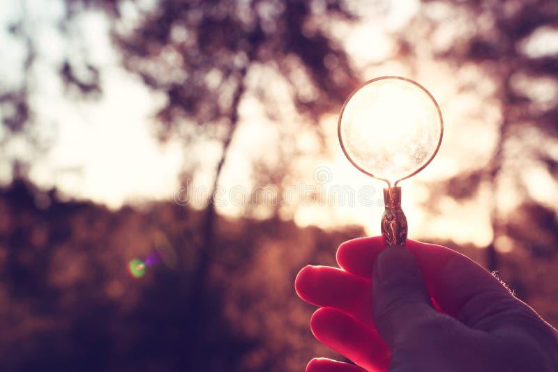 Uma mão masculina mantém uma lupa contra o sol de ajuste fora conceito da busca, do pensamento criativo e do uso da energia solar fotos de stock royalty free