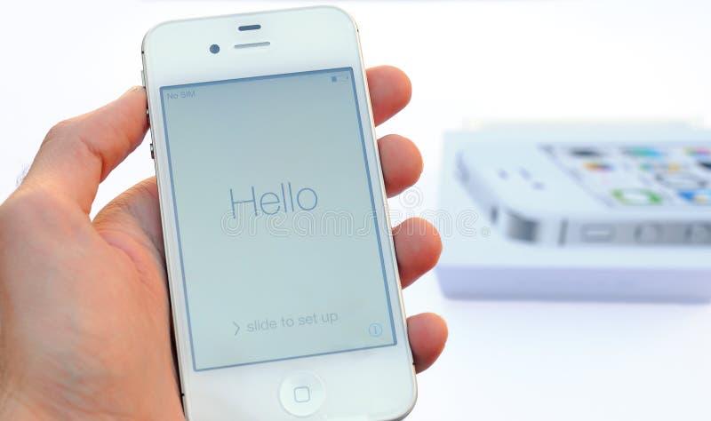 Uma mão masculina que guarda um dispositivo branco de Apple Iphone acima e um exemplo de Iphone no fundo, isolado no fundo branco imagem de stock royalty free