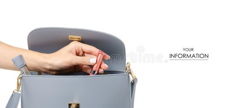 Uma mão pôs o brilho cosmético do bordo do batom no teste padrão cinzento azul fêmea do saco de couro imagens de stock royalty free