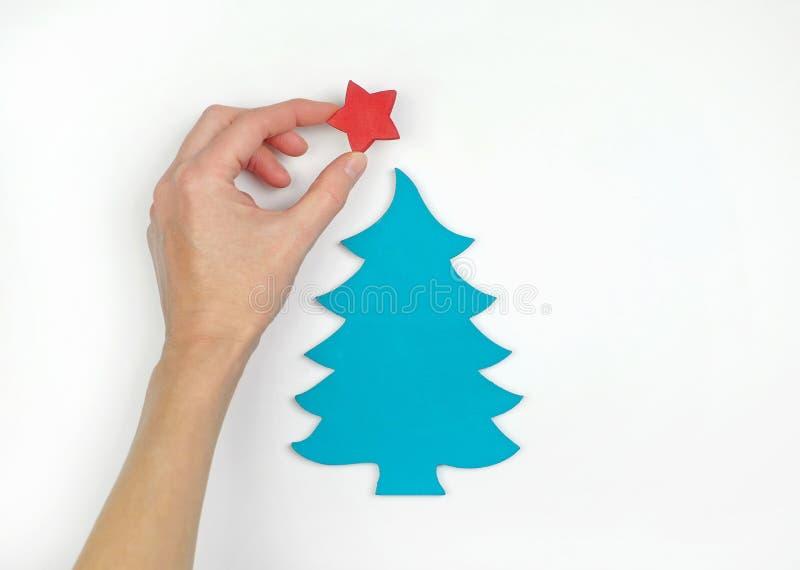 Uma mão que decora a árvore de Natal de madeira pequena com uma estrela, fundo branco Configuração lisa Vista superior fotografia de stock