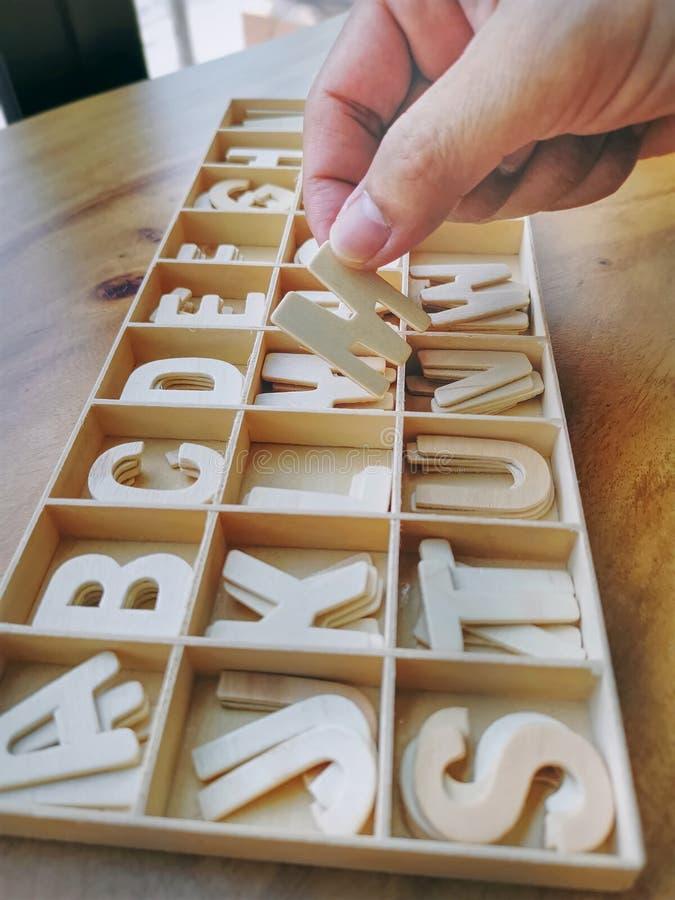 Uma mão que escolhe uma parte de alfabeto de madeira da bandeja foto de stock royalty free