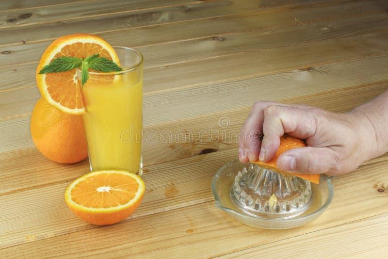 Uma mão que espreme o suco de uma laranja em um espremedor de frutas de vidro manual Ajuste em uma tabela planked de madeira imagens de stock royalty free