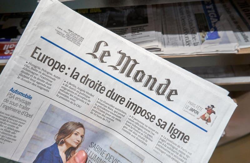 Uma mão que guarda o jornal de Le Monde imagens de stock royalty free