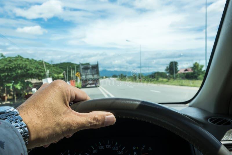 Uma mão que guarda o volante ao lado da estrada para a movimentação segura imagem de stock royalty free