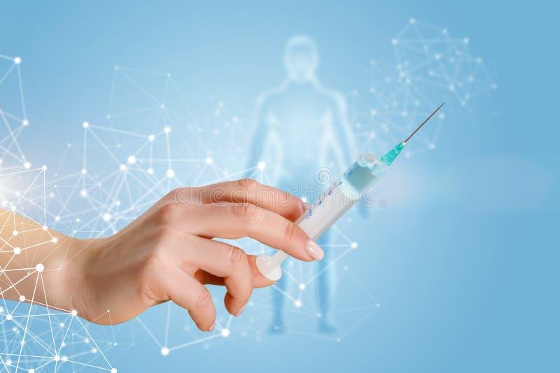Uma mão que guarda uma seringa da vacinação com substância imagens de stock