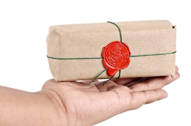 Uma mão que guarda um pacote selado foto de stock