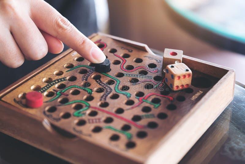 Uma mão que joga o jogo de madeira das serpentes e das escadas imagens de stock royalty free