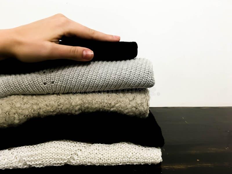 Uma mão que toca em uma pilha de camisetas coloridas de lãs aquece macio e confortável macios para vestir imagens de stock