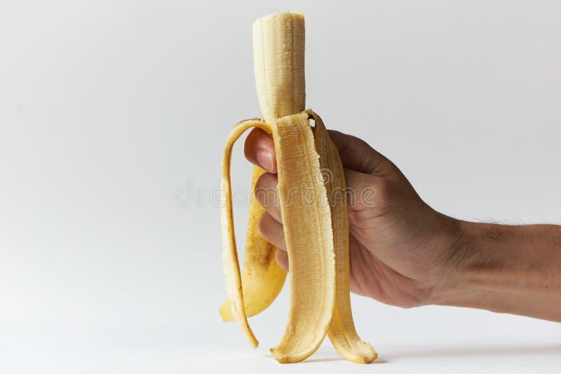 Uma mão segurando uma casca de banana caveprada imagens de stock royalty free