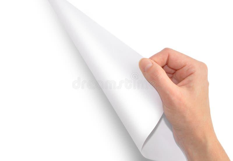 Uma mão turing um pedaço de papel branco fotografia de stock