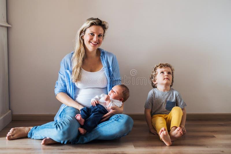 Uma m?e nova bonita com um beb? rec?m-nascido e seu irm?o em casa foto de stock