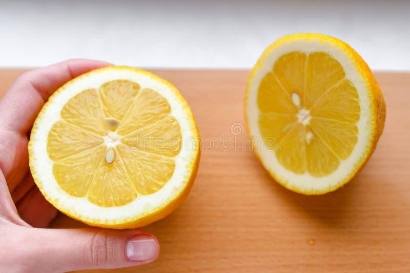 Uma m?o do ` s da mulher toma uma fatia de lim?o amarelo fresco org?nico em uma placa de corte de madeira Fatias de limão em uma  foto de stock