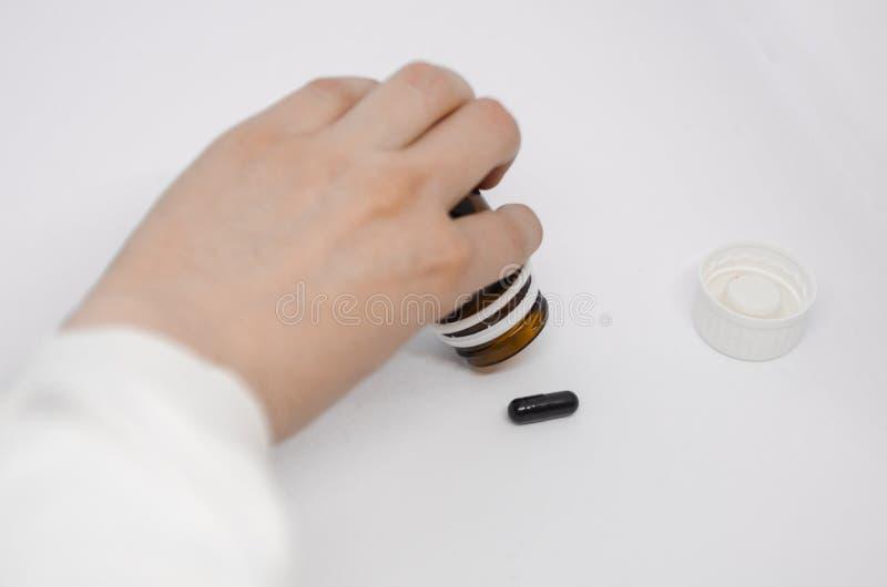 Uma m?o que derrama comprimidos fora da garrafa de comprimido imagem de stock