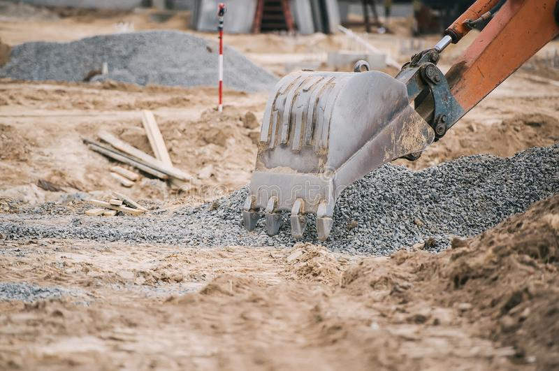 Uma m?quina escavadora na frente de uma pilha da entulho durante uma reconstru??o urbana foto de stock royalty free