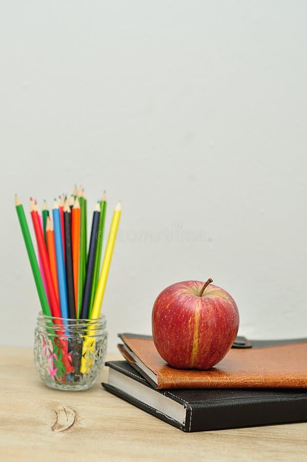 Uma maçã indicada com livros e lápis da coloração fotos de stock royalty free