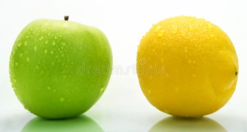 Uma maçã verde e um limão com gotas da água fotos de stock royalty free