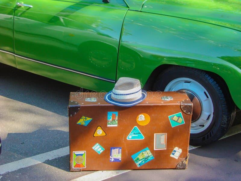 Uma mala de viagem velha em um fundo verde do carro foto de stock