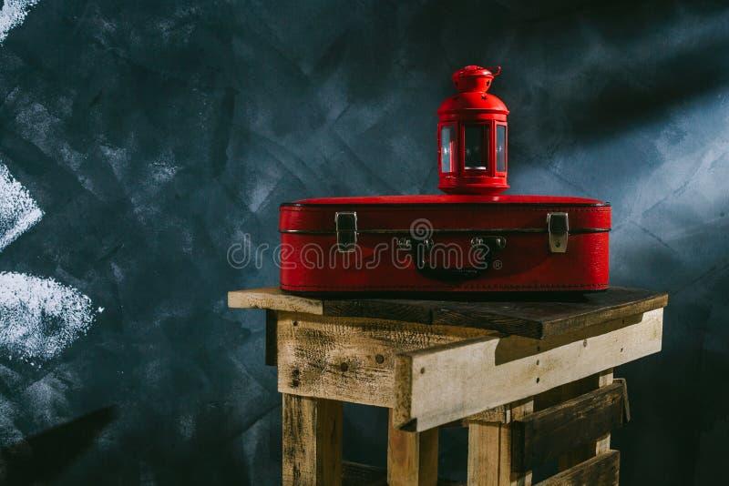 Uma mala de viagem vermelha e um castiçal vermelho em um fundo escuro fotos de stock