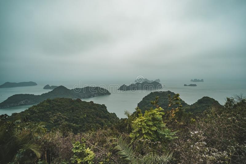 Uma manhã nublado escura e enevoada na baía de Halong, foto tonificada Paisagem bonita da montanha com o ponto de vista na ilha d foto de stock royalty free
