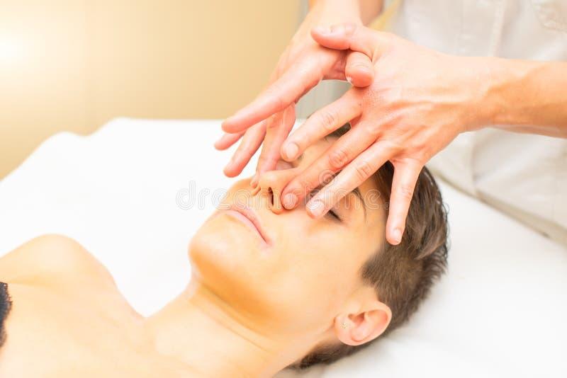 Uma massagem de relaxamento da beleza para uma jovem mulher com um detalhe do nariz imagens de stock royalty free