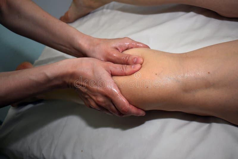 Uma massagem direita da vitela pelo terapeuta fotografia de stock royalty free