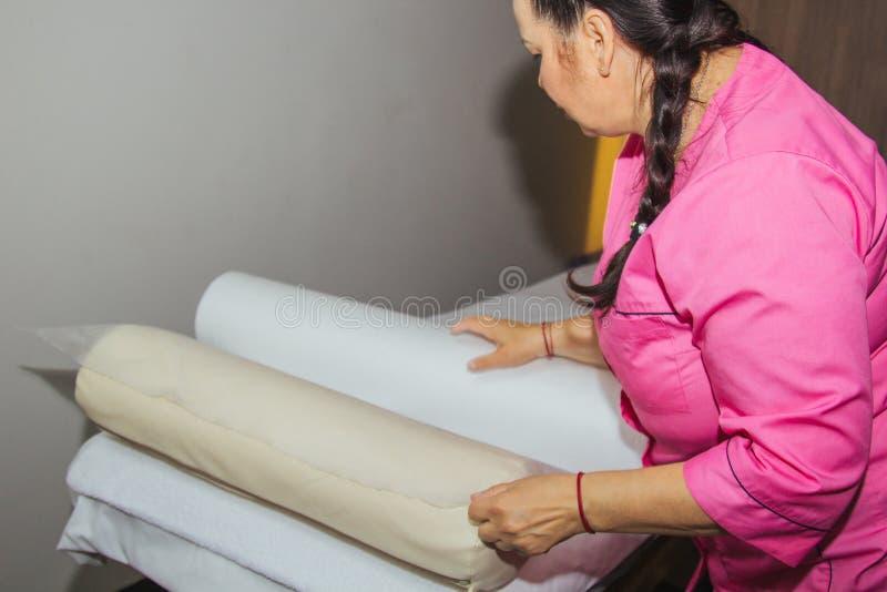 Uma massagista prepara um sofá para uma massagem, espalhando uma cama descartável na sala de massagens imagem de stock