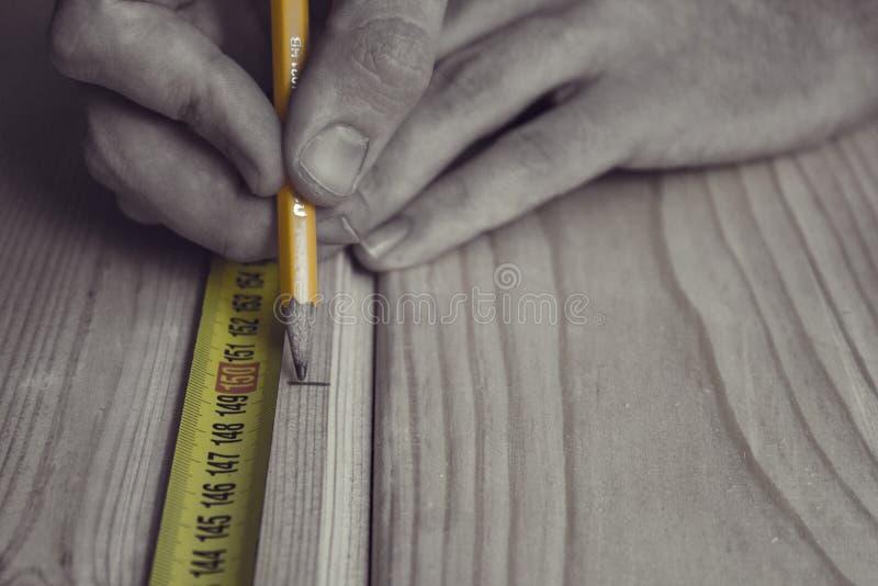 Uma medida do homem a distância usando a fita de medição fotos de stock royalty free
