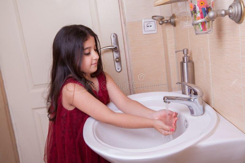 Uma menina árabe do Oriente Médio pequena bonita com vestido vermelho está lavando suas mãos no banheiro fotos de stock royalty free
