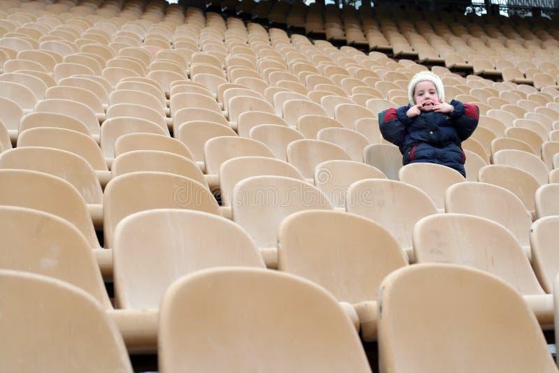 Uma menina é uma em fãs que vazios a zona no estádio faz careta imagem de stock