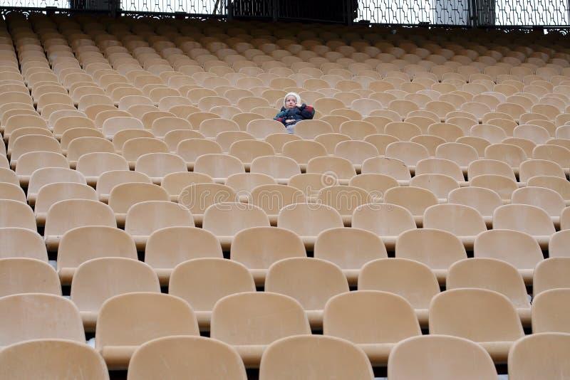 Uma menina é uma na zona vazia dos fãs no estádio imagem de stock