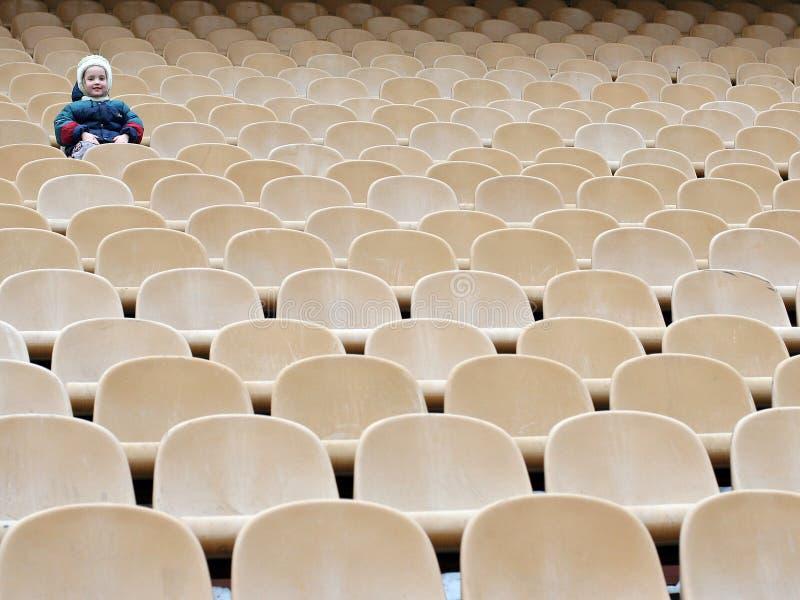Uma menina é uma na zona vazia dos fãs no estádio fotografia de stock